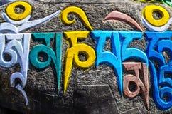 Tibetana buddistiska religiösa symboler på stenar Arkivbild