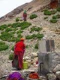 Tibetana män som får vatten på ett klapp, Rongbuk, Tibet, Kina arkivbilder