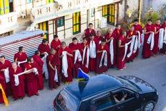 Tibetana munkar som bugar med virak, röker för välkomnande på hög nivå munk i bil det förbigå i område av den Rumtek kloster Fotografering för Bildbyråer