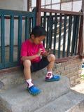 Tibetanische Flüchtlings-Kinder von Tibet spielt Handy in R lizenzfreie stockbilder
