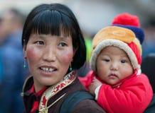 Tibetanische Frauen in der nationalen Kleidung, die Baby trägt Stockbilder