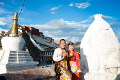 Tibetanische Paare im traditionellen Kostüm Stockfotos