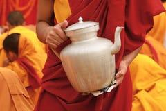 Tibetanische Teeteekanne in den Händen eines Mönchs in Nepal Lizenzfreie Stockfotos