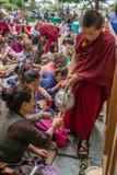 Tibetanischer Tee des Aufschlags des buddhistischen Mönchs zu den Zuhörern während seiner Heiligkeit der 14 Unterricht Dalai Lama Lizenzfreie Stockfotografie