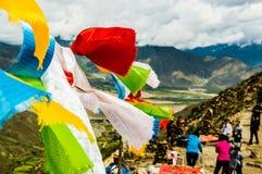 Tibetanisches Gebet kennzeichnet das Wellenartig bewegen in den Wind auf einem Durchlauf Lizenzfreies Stockfoto