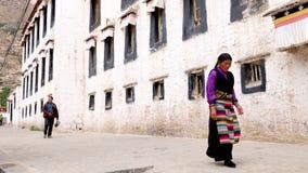 Tibetant förbigå ett lokalt hus Fotografering för Bildbyråer