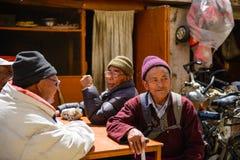 Tibetant folk Gamla tibetana män som sitter och talar utanför på gatan av den Leh staden, Ladakh, Indien Royaltyfri Bild
