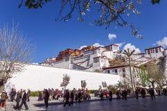 Tibetant vallfärdar cirkeln den Potala slotten - Lhasa, Tibet arkivfoto
