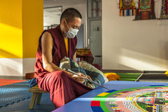 Tibetian monk constructing mandala from colored sand Royalty Free Stock Photography