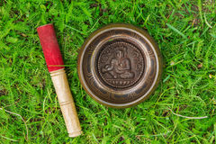 Tibetian singing bowl with wooden stick on the grass,. Stock Photography