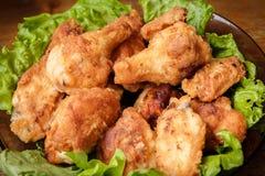 Tibias de poulet frit dans une croûte croustillante sur des feuilles de laitue dans un plat photographie stock libre de droits