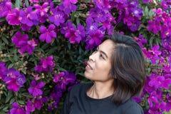 妇女和紫色花或Tibouchina granulosa在庭院里 免版税库存图片
