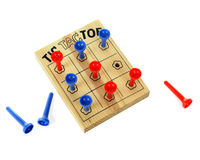 Tic Tac Toe. Close up image of a wooden tic-tac-toe game using plastic pegs.  Taken from above. Red wins!  On a white background Royalty Free Stock Images