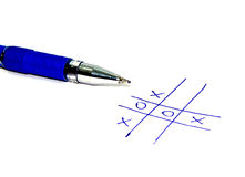 Noughts and crosses. Game of noughts and crosses (tic tac toe) with no clear winner and a blue biro pen, white background Royalty Free Stock Photography