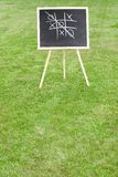 Tic-tac-toe. A chalkboard with tic-tac-toe game standing on the lawn. Space for copy Royalty Free Stock Images