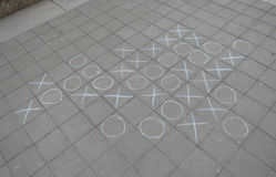 Tic tac toe. Aka noughts and crosses or Xs and Os, played with chalk on a pavement extended five in a row version Stock Photos