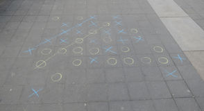 Tic tac toe. Aka noughts and crosses or Xs and Os, played with chalk on a pavement extended five in a row version Royalty Free Stock Photography