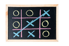 Tic tac toe on a black chalkboard stock photography