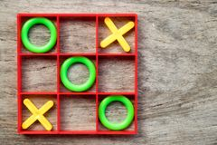 Tic-tac-toe board game with green O and yellow X in red frame on wood background. Cross, fun, design, win, competition, white, day, drawing, line, play stock photography