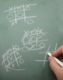 Tic Tac Toe on Chalk Board. Man's hand playing a game of tic tac toe on a chalkboard Stock Photography