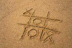 Tic-tac-toe drawing in sand background. Concept of winning and success Royalty Free Stock Photography