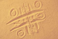 Tic-tac-toe drawing in sand background. Game on a beach Royalty Free Stock Photography