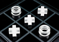 Tic-tac-toe game. Glass tic-tac-toe game on black background Royalty Free Stock Image