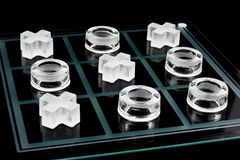 Tic-tac-toe game. Glass tic-tac-toe game on black background Royalty Free Stock Photography