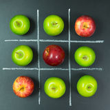 Tic tac toe game with apples. Tic tac toe game using apples on chalkboard Royalty Free Stock Images