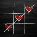 Tic tac toe game with chalk hearts, XO noughts and crosses Valentine`s Day style. Background Royalty Free Stock Photo