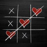 Tic tac toe game with chalk hearts, XO noughts and crosses Valentine`s Day style. Background Stock Photography