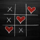 Tic tac toe game with chalk hearts, XO noughts and crosses Valentine`s Day style. On blackboard background Royalty Free Stock Photo