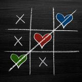 Tic tac toe game with chalk hearts, XO noughts and crosses Valentine`s Day style. On blackboard background Stock Image