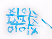 Tic tac toe. Game drawn with blue paint brush on white paper Stock Photography