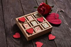 Tic tac toe game with hearts and xo letters as love game concept. Wooden tic tac toe game with red hearts and letters XO as love game concept for valentine`s day royalty free stock photo