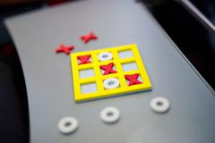 Tic tac toe game. Leisure activity for kids and adults. At home, traveling, on plane. Closeup of playing game Stock Photos