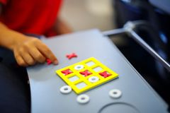 Tic tac toe game. Leisure activity for kids and adults. At home, traveling, on plane. Closeup of hands of child playing game Royalty Free Stock Image
