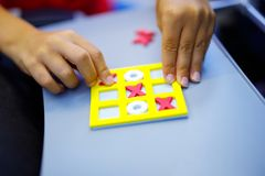 Tic tac toe game. Leisure activity for kids and adults. At home, traveling, on plane. Closeup of hands of child playing game Stock Photo