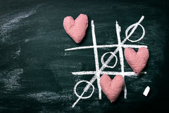 Tic Tac Toe Game. Love or Valentine`s Day Concept with Chalkboar. D and Hearts on a Old Dark Background. Top view with copy space Stock Photos