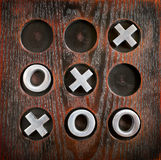 Tic Tac Toe. Game of Tic Tac Toe or Noughts and Crosses on a wooden board with metal pieces for success or winning concept Stock Photography