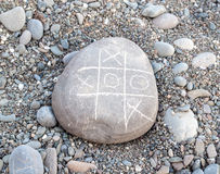 TIC TAC  toe game on a pebble Royalty Free Stock Photos