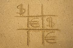 Tic-tac-toe game with playing euro and dollar symbols on sand. Concept of financial currency games Royalty Free Stock Images
