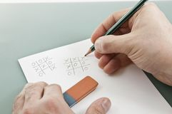 Tic tac toe game with right hand writer Stock Photos