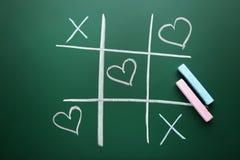 Tic tac toe game. Drawn by chalk on green school blackboard Royalty Free Stock Photos