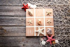 Tic tac toe game. By seashells and starfish on grey wooden table Stock Photos