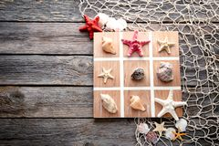 Tic tac toe game. By seashells and starfish on grey wooden table Royalty Free Stock Photo