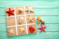 Tic tac toe game. By seashells and starfish on mint wooden table Stock Photos