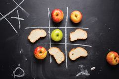 Tic-tac-toe Game Between Useful Harmful Product. Tic-tac-toe Choice Competition Game Between Useful Product Fruit Apple and Harmful Calories White Bread Food Stock Images