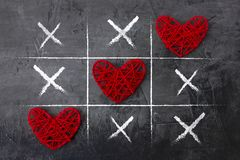 Tic Tac Toe game on Valentine`s day against a dark background. View from above Stock Images