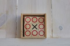 Tic-tac-toe game on white wooden background. Royalty Free Stock Images